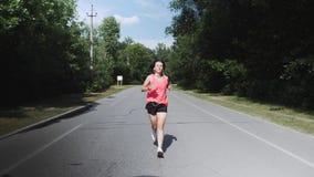 Junges dünnes Mädchen im rosa Hemd mit Kopfhörern beginnt, in Park zu laufen Brunette attraktive Frau mit dem ausgebildeten Körpe stock video footage