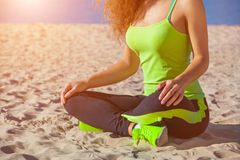 Junges dünnes Mädchen im schwarzen und hellgrünen Trainingsnazug, der nach einem Training im Sand auf der Küste sitzt Stockfotografie