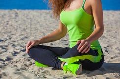Junges dünnes Mädchen im schwarzen und hellgrünen Trainingsnazug, der nach einem Training im Sand auf der Küste sitzt Stockbilder