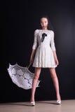 Junges dünnes Modell im hellen Sommerkleid mit einem mit Filigran geschmückten Regenschirm, der im Studio aufwirft Schwarzer Hint Stockbild