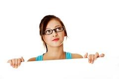 Junges denkendes Mädchen, das hinter Blatt Papier sich versteckt. Stockbilder