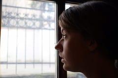 Junges deprimiertes Mädchen ist, schauend heraus denkend und das Fenster Sie ist traurig Stockbilder