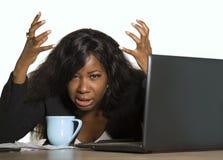 Junges deprimiertes und überwältigtes Geschäftsfrauarbeiten des Schwarzafrikaners amerikanisches frustriert am Bürocomputertisch- stockbild