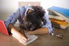 Junges deprimiertes und betontes Studentenmädchen, das mit dem Laptop- und Buchstapel überwältigt und frustriert, das Prüfungsgef lizenzfreies stockfoto