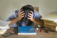 Junges deprimiertes und betontes Studentenmädchen, das mit dem Laptop- und Buchstapel überwältigt und frustriert, das Prüfungsgef lizenzfreies stockbild