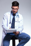 Junges Doktorsitzen und -schreiben Stockfotos