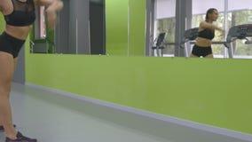 Junges Eignungsfrauentraining vor dem Spiegel an der Turnhalle Weiblicher Athlet, der vorher ihren Körper und Hände ausdehnt stock video