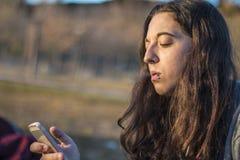 Junges ernstes Frauenporträt, ihr Telefon überprüfend und rauchen an der Dämmerung Lizenzfreies Stockfoto
