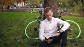 Junges ernstes kaukasisches Mannlesebuch, Sitzen auf dem städtischen Park der Grasstadt, herein studierend oder lesen, Freizeit stock footage