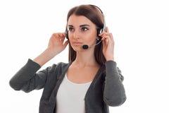Junges ernstes Mädchen in den Kopfhörern hält ihre Hände und blickt in Richtung Lizenzfreie Stockbilder