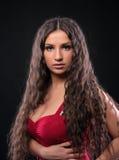 Junges erstaunliches Mädchen mit dem lockigen Haar im Rot Stockbild