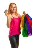 Junges erwachsenes Mädchen des Porträts mit farbigen Taschen halten Kreditkarte Stockfotos