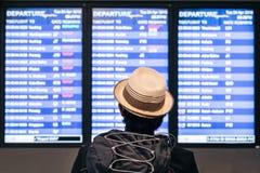 Junges erwachsenes touristisches Reisender backpaker, das Flughafenflugplanzeitplan auf dem Schirm betrachtet lizenzfreie stockfotos