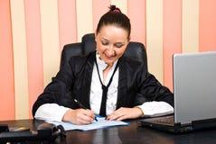 Junges Executivfrauenschreiben auf Papieren Stockfoto