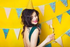 Junges feierndes Frauengrünkleid, ein Glas Champagner halten Stockfoto