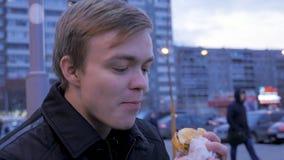 Junges Fleisch fressendes, einen geschmackvollen Schnellimbisshamburger am Straßenburger beißend Junges Fleisch fressendes ein Bu lizenzfreie stockfotos
