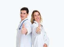 Junges freundliches Ärzteteam mit dem Daumen oben Lizenzfreie Stockbilder