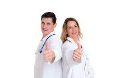Junges freundliches Ärzteteam mit dem Daumen oben Lizenzfreie Stockfotos