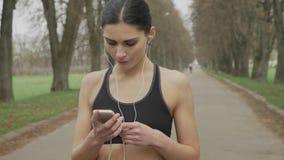 Junges fsport Mädchen schaltet Musik auf ihrem Smartphone, Betrieb, gesunder Lebensstil, Sportkonzeption ein stock video footage