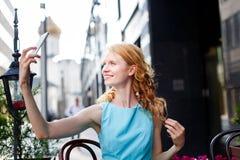Junges gelocktes blondes im blauen Kleid macht Foto auf Smartphone Stockfoto