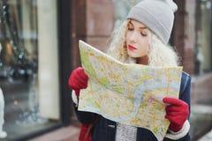 Junges gelocktes touristisches Mädchen mit Karte, Winter lizenzfreie stockfotos