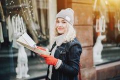 Junges gelocktes touristisches Mädchen mit Karte, Winter lizenzfreie stockfotografie