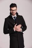 Junges Geschäft, das einen langen eleganten Mantel trägt Lizenzfreies Stockbild