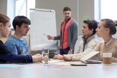Junges Geschäfts-Team, das am grauen Tisch mit Flip Chart sich bespricht stockfotografie