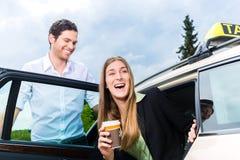 Junges Geschäftsfrauverlassen ein Taxi lizenzfreie stockbilder