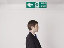 Junges Geschäftsmann-Standing Under Exit-Zeichen Stockfoto
