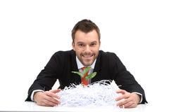 Junges Geschäftsmannsitzen- und -holdingschnittpapier Stockfoto