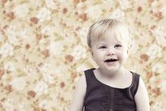 Junges gir, das gegen Blumenhintergrund lächelt Stockfotografie
