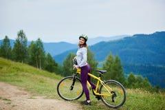 Junges glückliches Frauenreitfahrrad in den Bergen am Sommertag Lizenzfreies Stockfoto