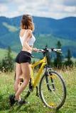 Junges glückliches Frauenreitfahrrad in den Bergen am Sommertag lizenzfreie stockbilder