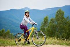 Junges glückliches Frauenreitfahrrad in den Bergen am Sommertag lizenzfreies stockbild