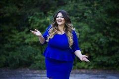 Junges glückliches Lächeln schön plus Größenmodell im blauen Kleid draußen, xxl Frau auf Natur Stockfoto