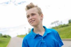 Junges glückliches lächelndes blondes Kind des männlichen Jungenjugendlichen draußen im Sommersonnenschein, der ein blaues Sweats Stockbild