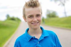 Junges glückliches lächelndes blondes Kind des männlichen Jungenjugendlichen draußen im Sommersonnenschein, der ein blaues Sweats Stockfoto