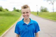 Junges glückliches lächelndes blondes Kind des männlichen Jungenjugendlichen draußen im Sommersonnenschein, der ein blaues Sweats Stockbilder