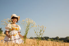 Junges glückliches Mädchen, das auf einem Weizengebiet und Auswahlblumen geht Stockbild