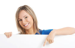 Junges glückliches Mädchen, das auf Kopienraum zeigt. stockfoto