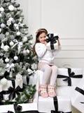 Junges glückliches Mädchen, das nahe verziertem Weihnachtsbaum mit pres sitzt Lizenzfreies Stockbild