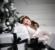 Junges glückliches Mädchen, das nahe verziertem Weihnachtsbaum mit pres sitzt Lizenzfreies Stockfoto