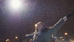 Junges glückliches Mädchen genießt den fallenden Schnee und hebt seine Hände an kalt Winter stock footage