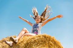 Junges glückliches Mädchen mit dem langen blonden Haar, das auf Heuschobern auf einem Gebiet des reifen Weizens sitzt Stockfoto
