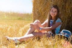 Junges glückliches Mädchen mit dem langen blonden Haar, das unter einem Heuschober auf einem Gebiet des reifen Weizens sitzt Stockfoto