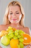 Junges glückliches Mädchen mit einer Platte der saftigen Früchte Lizenzfreies Stockbild