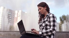 Junges glückliches Mädchen mit Laptop in der Stadt sitzt nahe dem Brunnengetränkkaffee stock video footage
