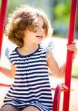 Junges glückliches Mädchen schwingt im Spielplatz Lizenzfreie Stockbilder