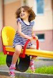 Junges glückliches Mädchen schwingt im Spielplatz Lizenzfreies Stockfoto